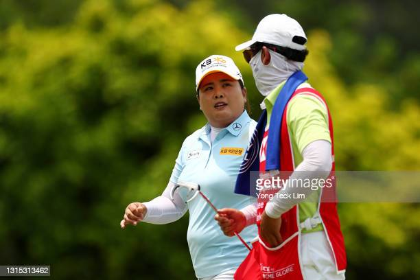 Inbee Park of South Korea speaks to her husband and caddie Gi Hyeob Nam after sinking her putt on the 13th green during the second round of the HSBC...