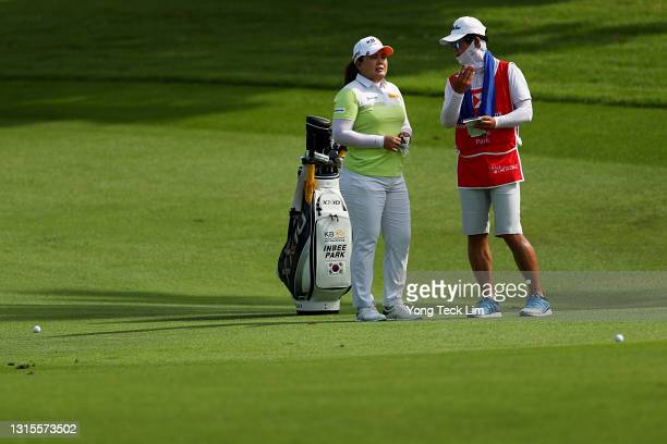 Inbee Park of South Korea speaks with her husband and caddie Gi Hyeob Nam as she waits to play her second shot on the second fairway during the third...