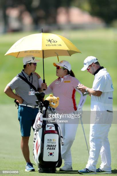 Inbee Park of South Korea waits with her husband Gi Hyeob Nam and her caddie Brad Beecher before she played her second shot on the 12th hole during...