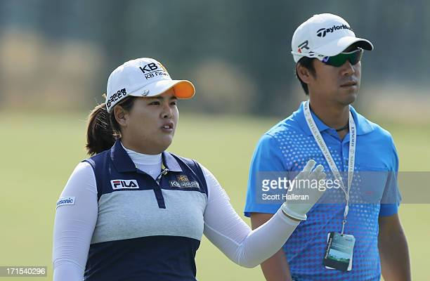 Inbee Park of South Korea walks alongside Gi Hyeob Nam, her coach and fiancé during a practice round prior to the start of the 2013 U.S. Women's Open...