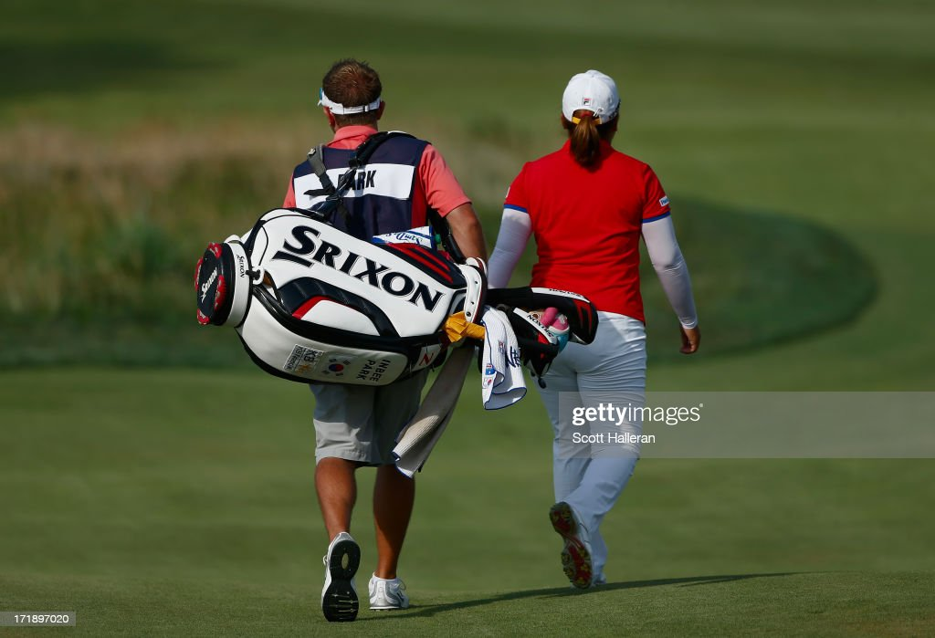 Inbee Park of South Korea walks with her caddie Brad Beecher to the 16th green during the third round of the 2013 U.S. Women's Open at Sebonack Golf Club on June 29, 2013 in Southampton, New York.