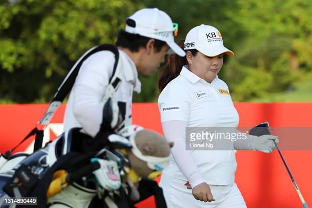 Inbee Park of South Korea walks with her caddie Gi Hyeob Nam after playing her shot on the first tee during a pro-am tournament prior to the HSBC...