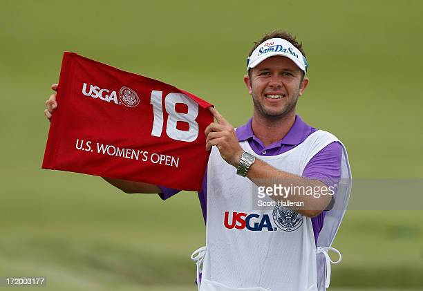 Inbee Park's caddie Brad Beecher poses with the 18th green flag after Park's four-stroke victory at the 2013 U.S. Women's Open at Sebonack Golf Club...