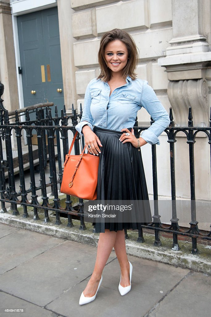 Inbetweeners actress Emily Atack wears a Topshop shirt and skirt, Micheal Kors bag, and Dorothy Perkins shoes. on February 24, 2015 in London, England.