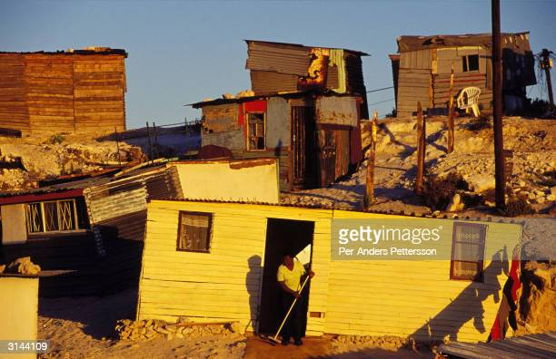 Inbluyezi Bane sweeps a rug outside her home June 23, 2001 in Site B Khayelitsha, a township about 35 kilometers outside Cape Town, South Africa....