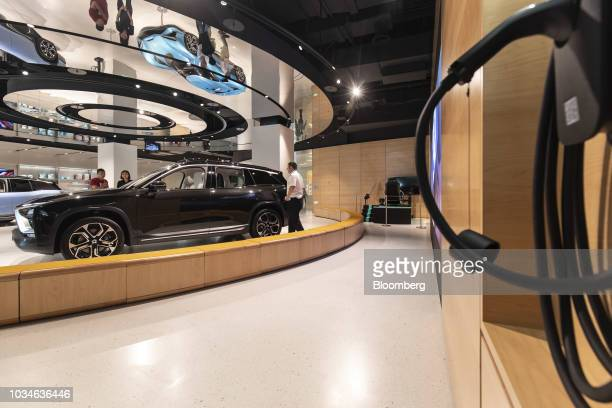 Inc ES8 sportutilityvehicle left and an electric vehicle charging unit right stand on display inside the Nio House showroom at the Shanghai Tower...