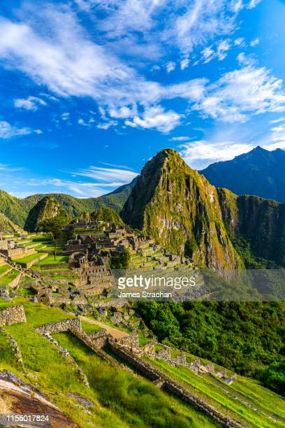 inca ruins of machu picchu in early morning light against dramatic blue sky and cloudscape, unesco world heritage site, sacred valley, peru - マチュピチュ ストックフォトと画像
