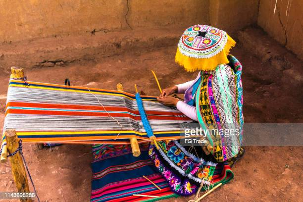 inca woman weaving alpaca wool - woven stock photos and pictures