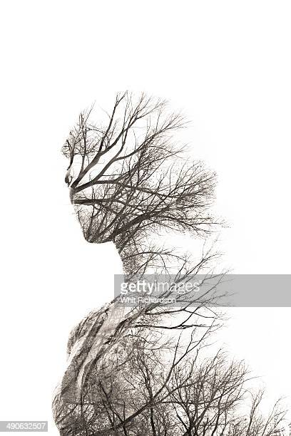 In-camera double exposure of woman and trees.