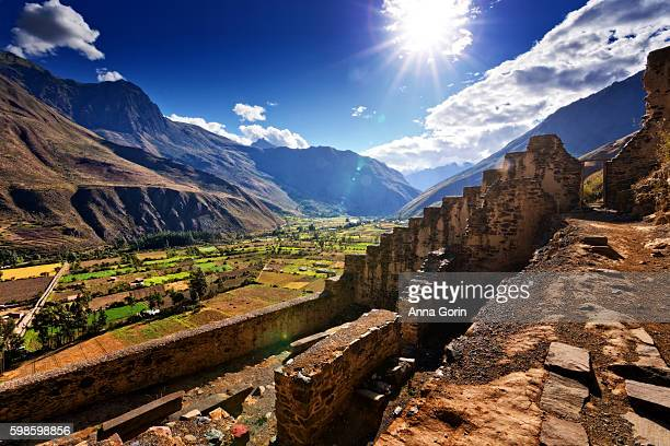 Incan ruins at Ollantaytambo in Sacred Valley of Peru, sunburst over surrounding mountains