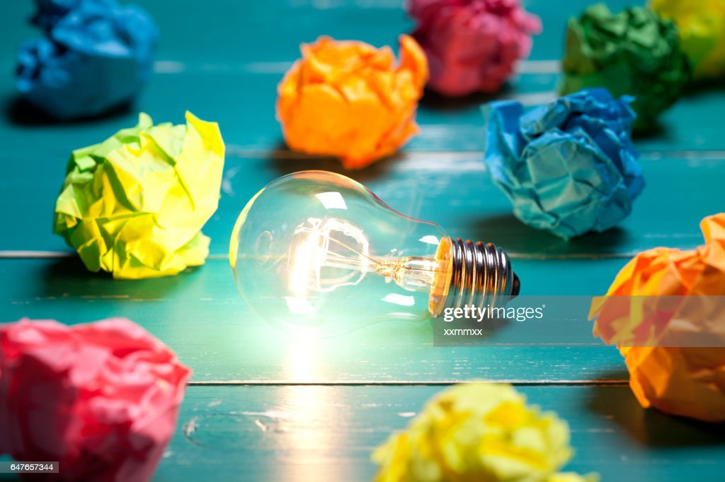 Incandescent bulb and colorful notes on turquoise wooden table : Stock Photo