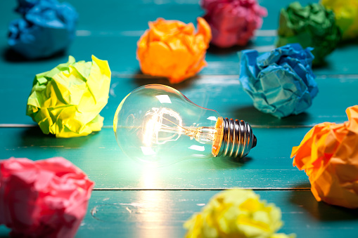 Incandescent bulb and colorful notes on turquoise wooden table - gettyimageskorea