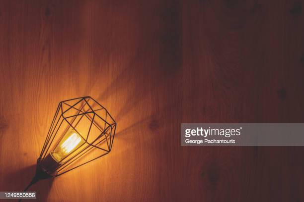 incandescent lamp on wooden surface - george wood stock pictures, royalty-free photos & images