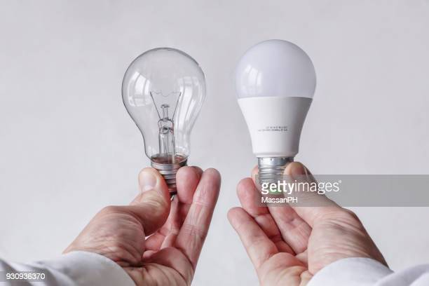 incandescent light bulb and led lamp being compared - comparison stock pictures, royalty-free photos & images