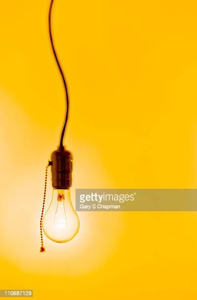 Incandescent lightbulb on yellow background