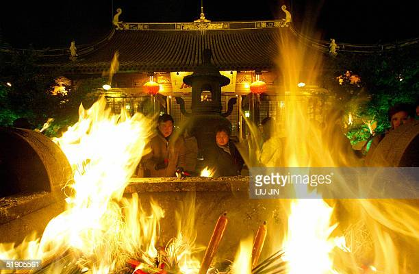 Incense and candles blaze as pilgrims watch during the New Year's celebrations at Longhua Temple in Shanghai 01 January 2005 For Chinese when the new...