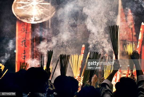 Incense coils are burnt as an offering to the sea goddess in a temple in Ho Chi Minh City in Vietnam Men wear goggles to protect their eyes from the...