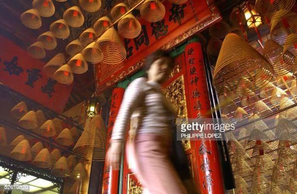 Incense coils hang from the ceiling of the Man Mo temple in Hong Kong 09 April 2005 as a woman carrying incense sticks walks by The temple a remnant...