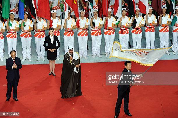 Incheon Mayor Song Younggil of South Korea waves the Asian Games flag while Kuwaiti Sheikh Ahmad alFahad alSabah president of the Olympic council of...
