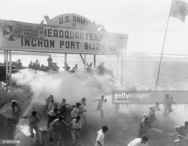 Inchon, Korea: American troops guarding the Wolmi Gateway to the compound housing U.N. Supervisory Commission Inspectors use tear gas and water hoses...