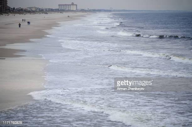 incidental people at jacksonville beach before the ocean storm. florida, usa - waterlijn stockfoto's en -beelden