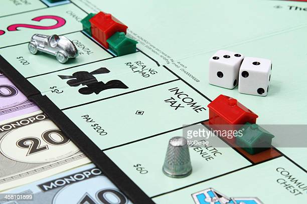 income tax square on monopoly board game - thimble stock photos and pictures