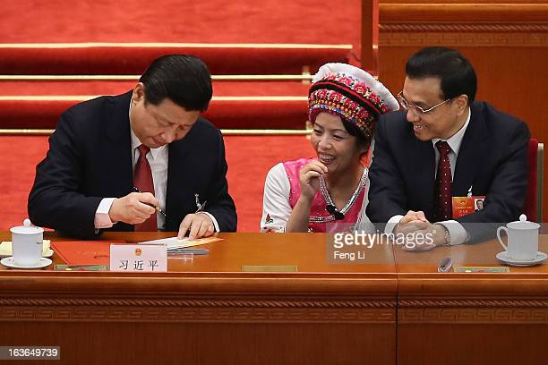 Incoming Chinese President Xi Jinping and Vice Premier Li Keqiang sign an autograph for an Ethnic minority delegate during the fourth plenary meeting...