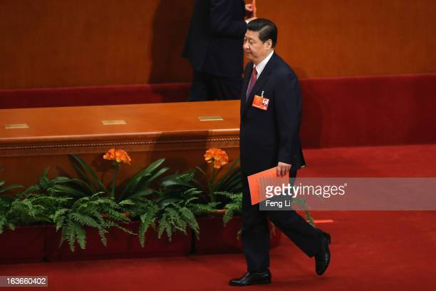 Incoming Chinese President Xi Jinping walks on the way to cast his vote into a box during the fourth plenary meeting of the National People's...