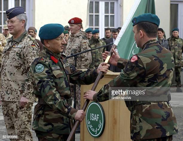 Incoming Commander Lieutenant General Ethem Erdagi hands the International Security Assistance Force flag to a Turkish soldier as German General...
