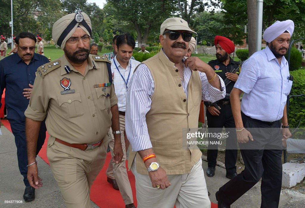 Incoming Governor of the northern Indian state of Punjab VP Badnore walks with officials as he arrives in Amritsar on August 23 2016 / AFP / NARINDER.