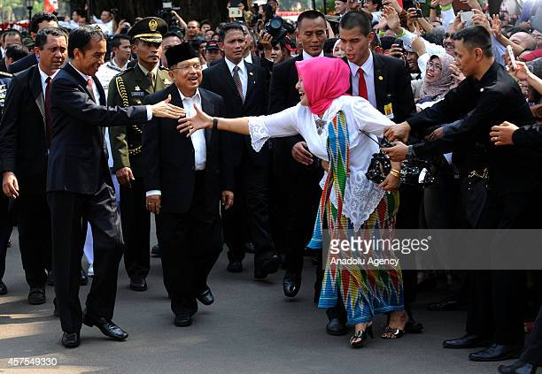 Incoming Indonesian President Joko Widodo shakes hand with a woman upon his arrival to the inauguration ceremony at the House of Representatives in...