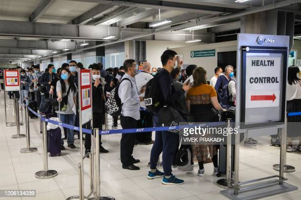 Incoming passengers line up to have their temperatures taken and health assessed at a checkpoint for people flying in from a list of countries and...