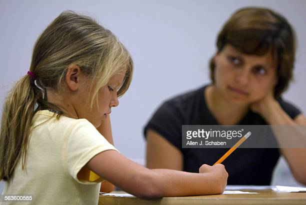 Incoming third–grader Emma McKay of Tustin left takes a reading test with teacher Christine Van duzer right Saturday July 24 2004 the first day of...