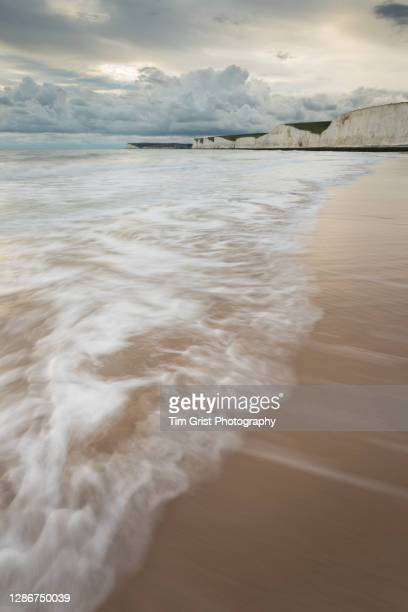 incoming tide at the seven sisters cliffs, east sussex, uk - cliff stock pictures, royalty-free photos & images