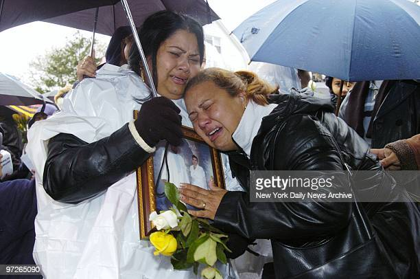 Inconsolable family members one crying Papi Papi mourn their loved ones during a rainy memorial service at Newport Ave and Beach 131st St in Belle...