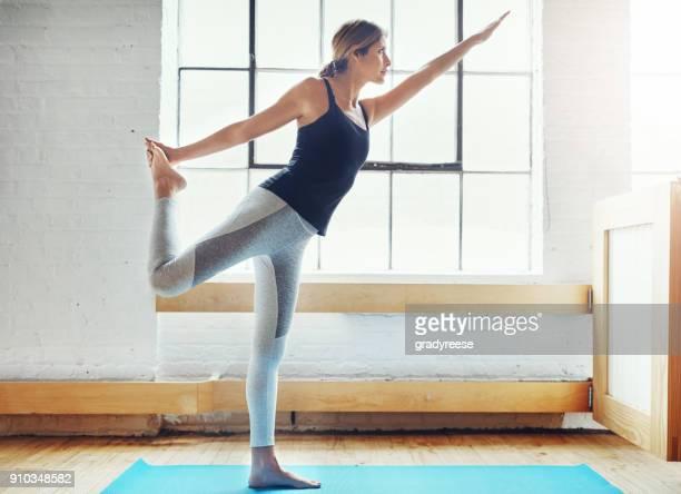 verbeteren van haar flexibiliteit, de kracht en de toon door middel van yoga - mattone stockfoto's en -beelden