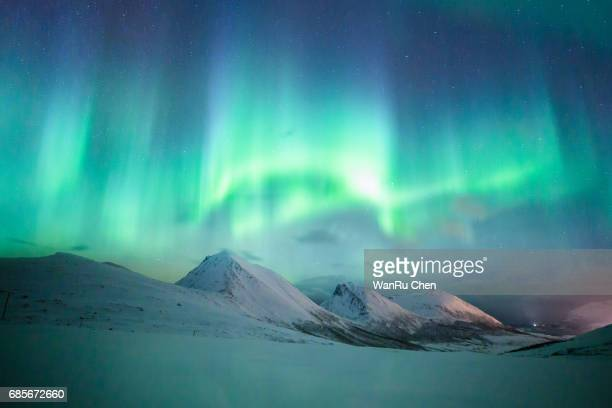 incredible aurora borealis activity above the coast in norway - poolklimaat stockfoto's en -beelden