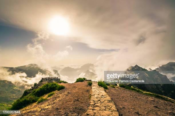 incredible high mountain landscape in madeira, pico do arieiro. with a dirt road above the clouds - paisaje escénico fotografías e imágenes de stock