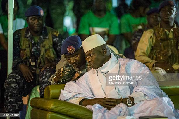 Incumbent Gambian President Yahya Jammeh listens to one of his aides in Banjul on November 29 during the closing rally of the electoral campaign of...