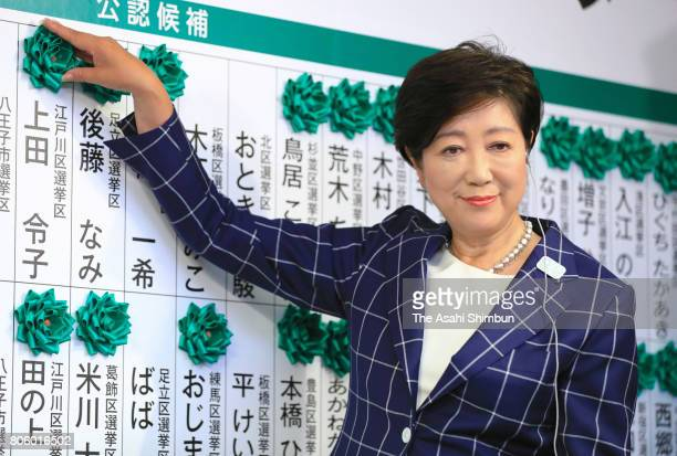 Incumbent Tokyo Metropolitan Governor and Tomin First no Kai party leader Yuriko Koike puts a paper flowers on names of candidates who won the seats...