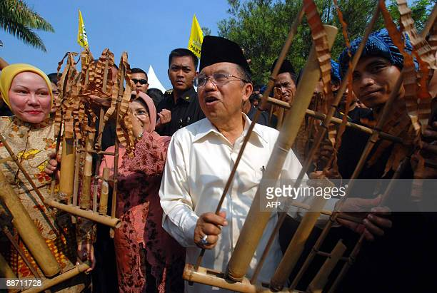 Incumbent Vice President Jusuf Kalla holds a traditional music instrument Angklung Buhun next to his spouse Mufidah Jusuf Kalla and Banten Governor...