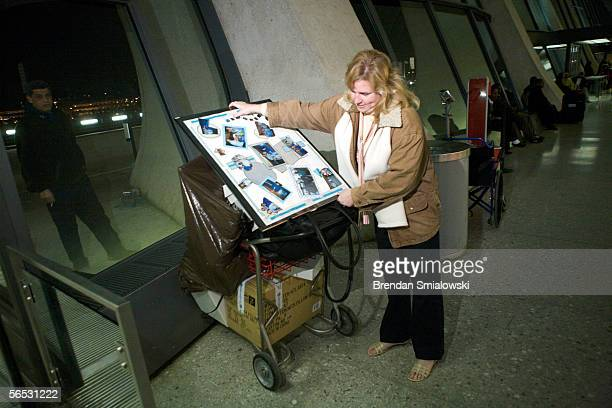Independence Air supervisor Karen Daley places a collage of photos from the opening day of the airline on a baggage cart while leaving Dulles...
