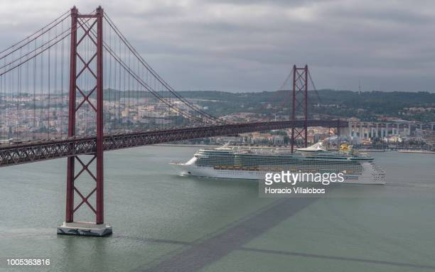 Independence of the Seas a Freedomclass cruise ship operated by the Royal Caribbean cruise line sails under 25 de Abril bridge on the Tagus River...