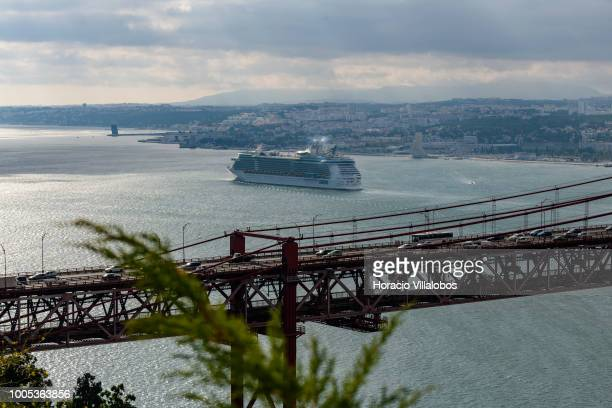 Independence of the Seas a Freedomclass cruise ship operated by the Royal Caribbean cruise line sails past 25 de Abril bridge on the Tagus River...