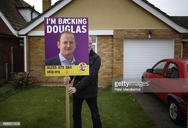 Independence Party candidate Douglas Carswell installs a placard in the garden of a supporter on April 8 2015 in ClactononSea England Mr Carswell was...