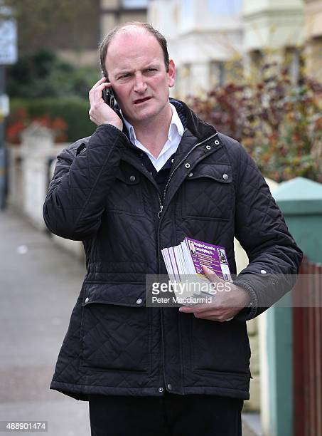 Independence Party candidate Douglas Carswell talks to a supporter on the phone as he distributes leaflets to homes in the town centre on April 8...