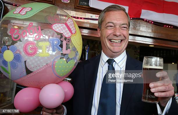Independence Party leader Nigel Farage celebrates the arrival of the new royal baby with a 'baby Girl' balloon in a pub on May 2 2015 in Ramsgate...