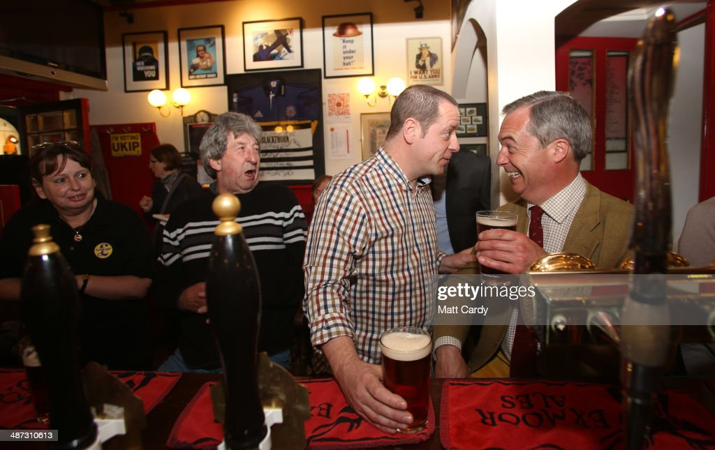 UK Independence Party leader Nigel Farage (R) enjoys a pint with Paul Alvis, the landlord of Volunteer Rifleman's Arms, as he visits Bath to meet with party members, candidates and supporters on April 29, 2014 in Bath and North East Somerset, England. Nigel Farage visited Bath as part of the UKIP tour ahead of next month's European elections.
