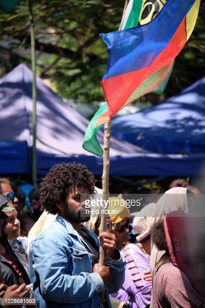 Independence supporter Ricardo carries a flag of the Socialist Kanak National Liberation Front as he takes part in a symbolic day marking the taking...