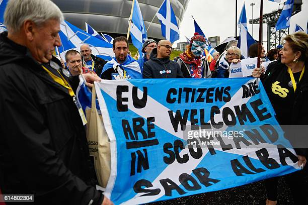 Independence supporters hold up a banner stating that EU citizens are welcome in Scotland as they take part in a rally outside the Scottish National...